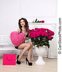 Happy smiling beautiful girl holding heart over pink bouquet of roses and shopping gift. Valentine day love concept.