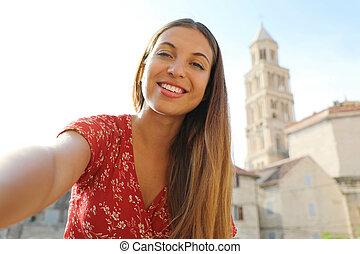 Happy smiling beautiful girl take self portrait in Split, Croatia, Europe