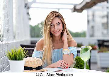 Happy smiling beautiful girl with long hair. A woman in a summer cafe on veranda of the restaurant. Sits at a table in a blue dress, close-up. Emotions of joy, enjoyment and comfort from work done.