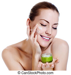 Happy smiling beautiful woman applying moisturizer cream on...