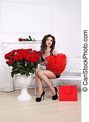 Happy smiling beautiful woman holding red heart over bouquet of roses and shopping gift. Valentine day love concept