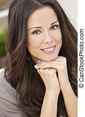 Portrait of a beautiful brunette young woman with perfect teeth smiling and resting on her hands