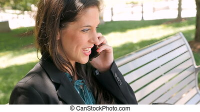 Happy smiling beautiful woman talking on smart phone on park bench outside