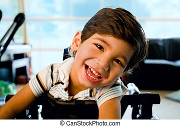Happy smiling biracial disabled little boy standing in walker