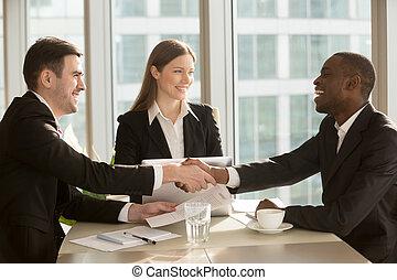 Happy smiling black and white businessmen handshaking after sign