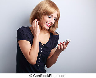 Happy smiling blond woman reading sms in mobile phone on blue background