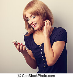 Happy smiling blond woman reading sms in mobile phone. Toned closeup portrait