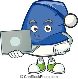 Happy smiling blue christmas hat cartoon character working with laptop