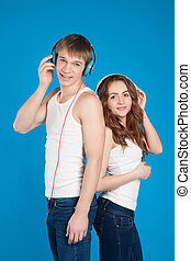 happy smiling boy and girl listening music in headphones in the studio over blue background