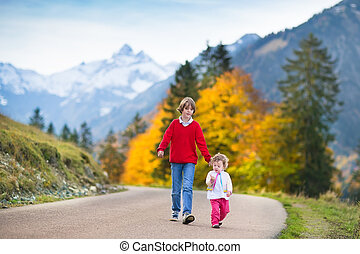 Happy smiling boy and his little baby sister walking on a road b