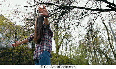 Happy smiling brunette woman in checkered shirt turning with arms outstretched outdoors