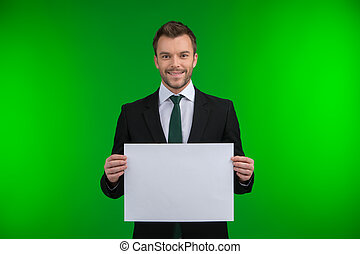 Happy smiling business man holding blank signboard. Young guy standing isolated over green background