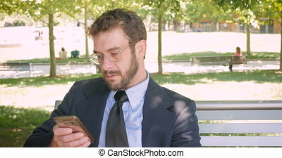 Happy smiling business man reading emails or social media posts on smart phone