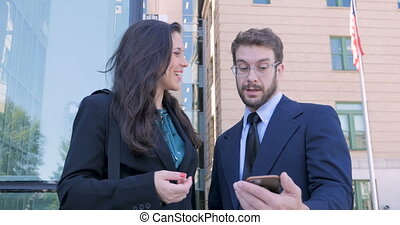 Happy smiling business partners looking at smart phone shake hands and leave