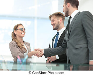 Happy smiling business people shaking hands after a deal in offi