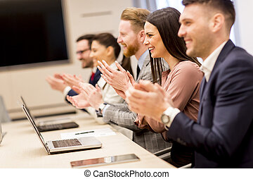 Happy smiling business team clapping hands