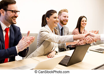 Happy smiling business team clapping hands during a meeting