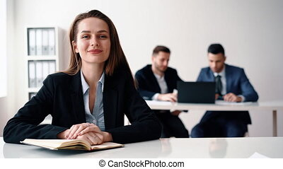 Happy smiling business woman sitting in office with her business team