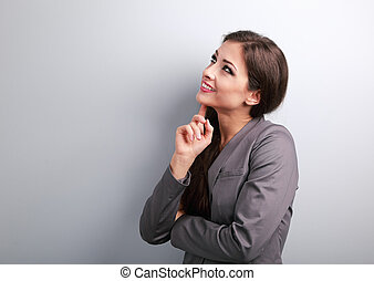 Happy smiling business woman thinking and looking up on blue background
