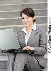 Happy smiling business woman using laptop