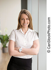 Happy smiling businesswoman looking at camera with arms crossed,