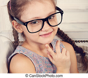 Happy smiling calm kid girl in eyeglasses looking and thinking about. Closeup toned studio portrait