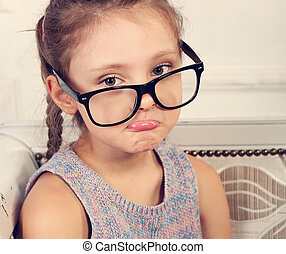 Happy smiling calm kid girl in eyeglasses looking and thinking about with grimacing fun face. Closeup toned portrait