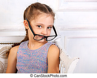 Happy smiling calm kid girl in eyeglasses looking. Closeup studio portrait