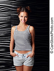 Happy smiling casual hispanic woman posing in blue shorts and top on black wall background