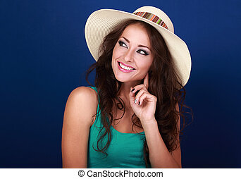 Happy smiling casual makeup woman in summer hat thinking and looking on bright blue background