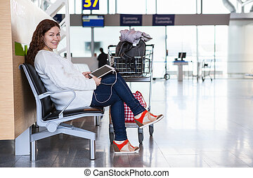 Happy smiling Caucasian woman with devices sitting in airport lounge