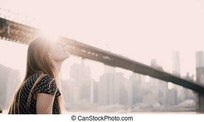 Happy smiling Caucasian young woman sitting on river embankment fence, enjoying New York Brooklyn Bridge panorama 4K.