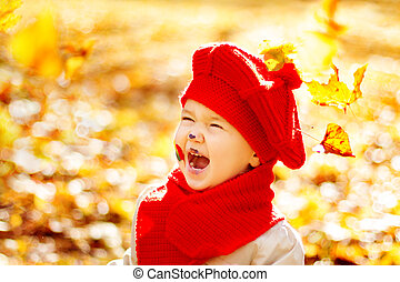 Happy smiling child in autumn park enyoing sunshine