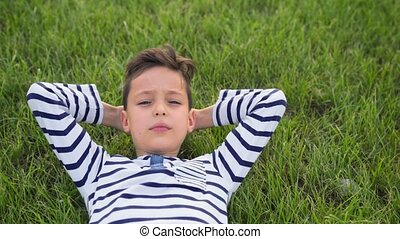 Happy smiling child lie on green grass relaxed.