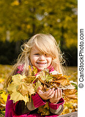 happy smiling child with colorful autumn leavea
