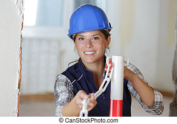 happy smiling construction woman working with chains