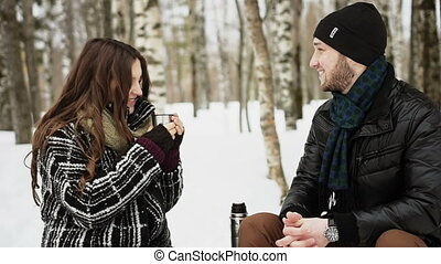 Happy smiling couple in a park drinking tea in winter