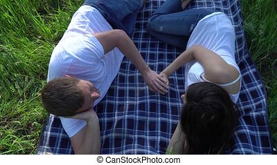 Happy smiling couple lying on grass and relaxing