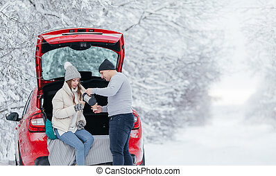 Happy smiling couple of travelers drink coffee or tea with a thermos standing near the red car in the winter forest