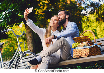 Happy smiling couple on a picnic makes selfie.