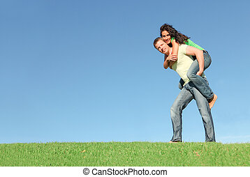 happy smiling couple outside on grass giving piggy back in...