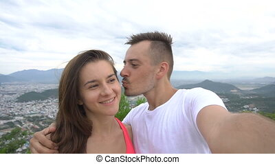Happy smiling couple recording video, taking selfie in the mountains with aerial city view. Man kisses girl