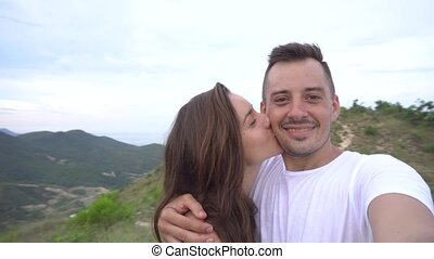 Happy smiling couple recording video, taking selfie in the mountains with aerial city view. Woman kisses man