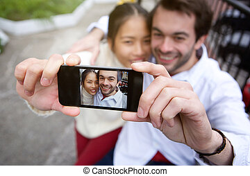 Happy smiling couple taking selfie outdoors