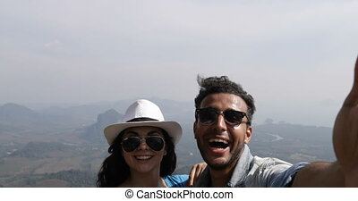 Happy Smiling Couple Taking Selfie Photo On Mountain Top Over Beautiful Landscape POV, Mix Race Man And Woman Tourists