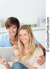 smiling couple using tablet at home