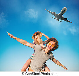 Happy smiling couples playing at the beach with aircraft in...