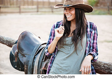 Happy smiling cowgirl in hat holding straw in mouth while...