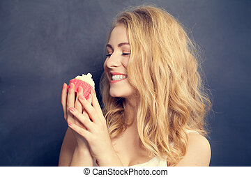 Happy smiling cute woman eat sweet cake on black background.