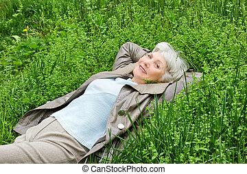 Happy smiling elderly woman lying on green grass meadow